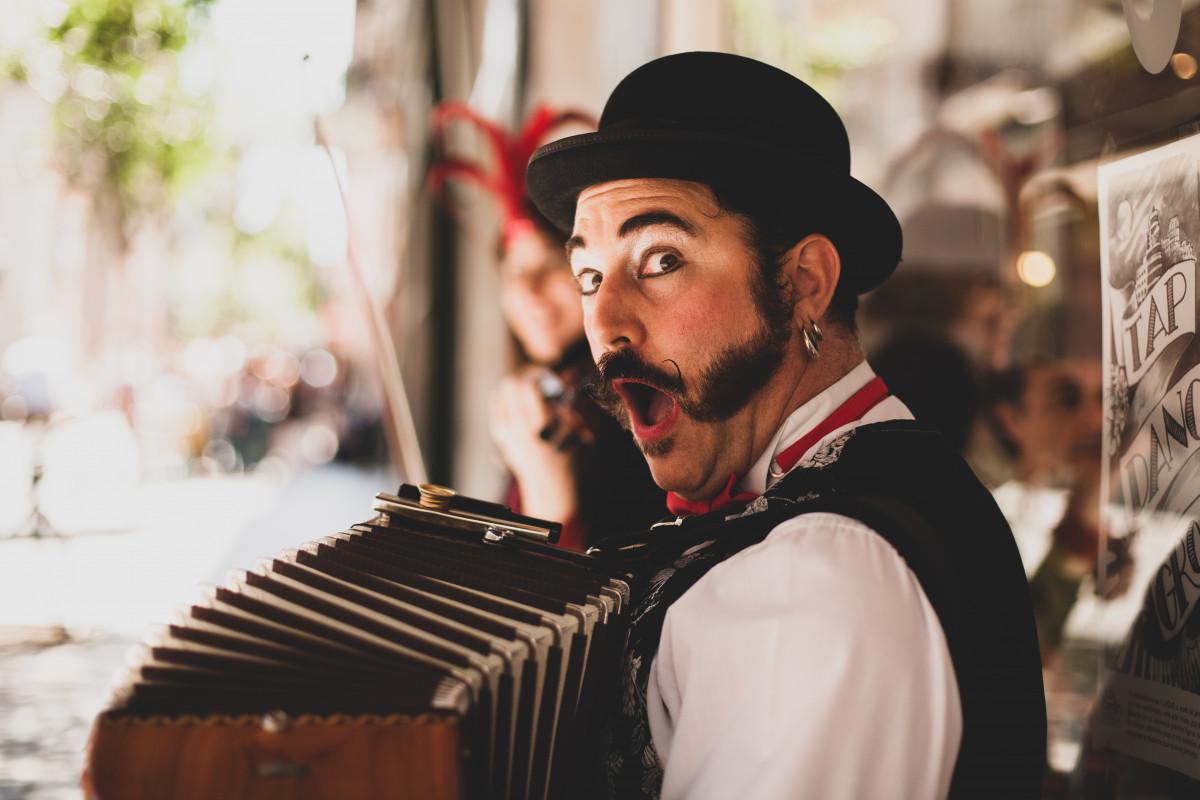 Un uomo truccato da clown suona la fisarmonica